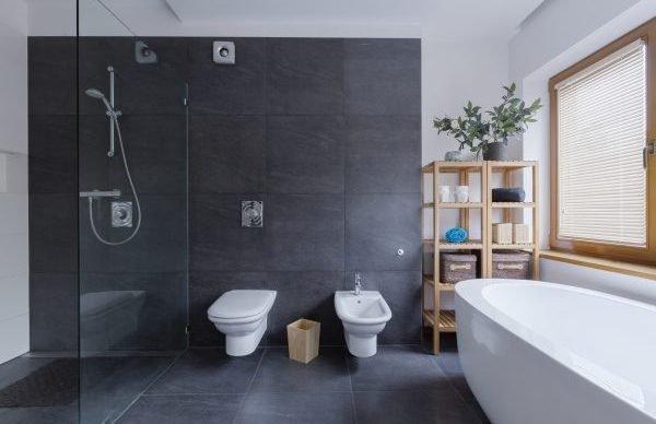 Glass floor shower in modern black bathroom interior with travertine walls in wellness spa center