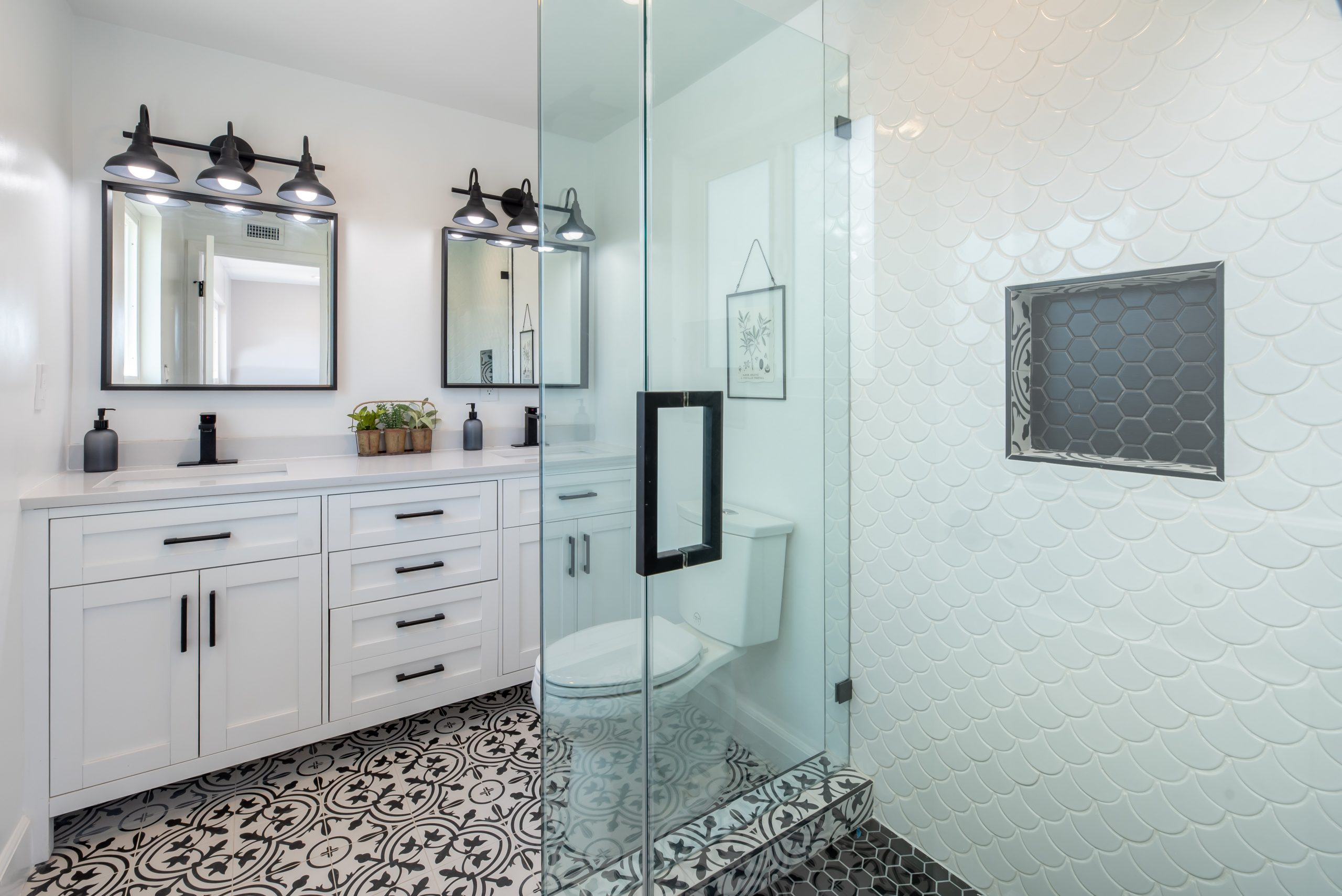 geometric black and white floor tiles with a glassed shower and three lights over each sink in this san diego bathroom remodel