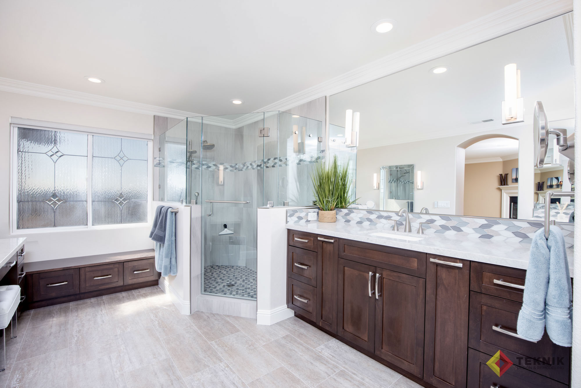 Remodeled bathroom with corner glass shower, dual sinks, dark cabinets and white countertops