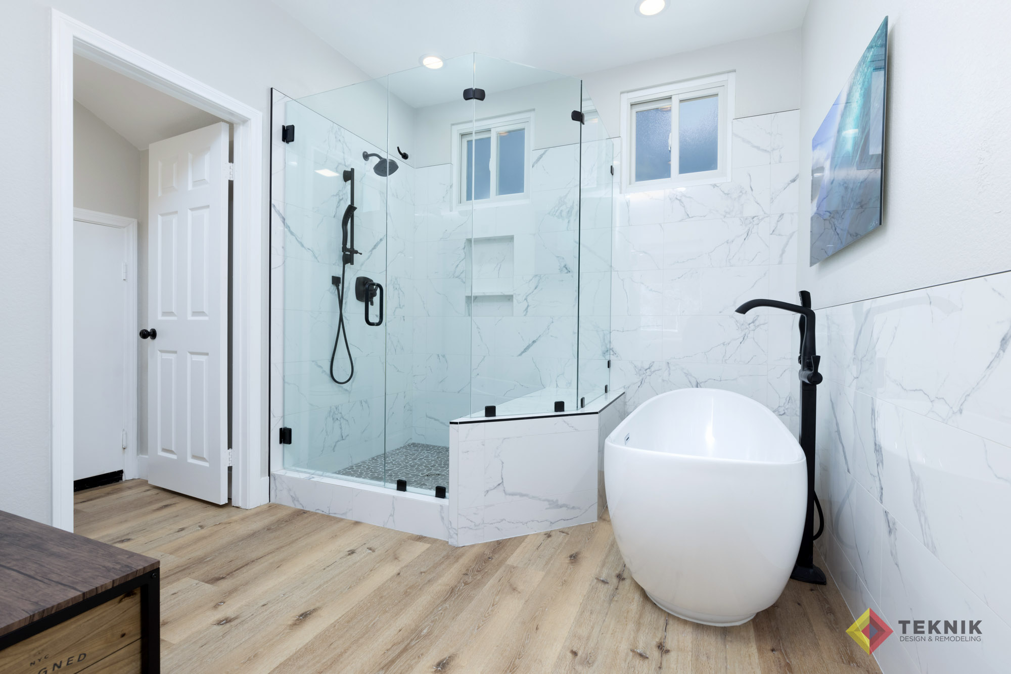 white marble bathroom tile and tub with a glass shower and pine flooring a san diego bathroom remodel